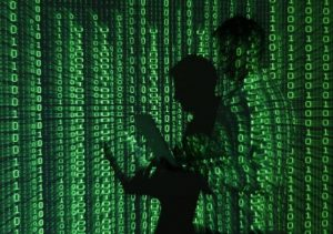 An illustration picture shows a projection of binary code on a man holding a laptop computer, in an office in Warsaw June 24, 2013. REUTERS/Kacper Pempel